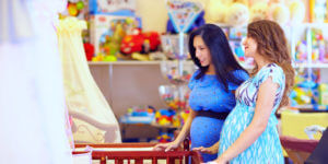 pregnant women choosing cot for baby